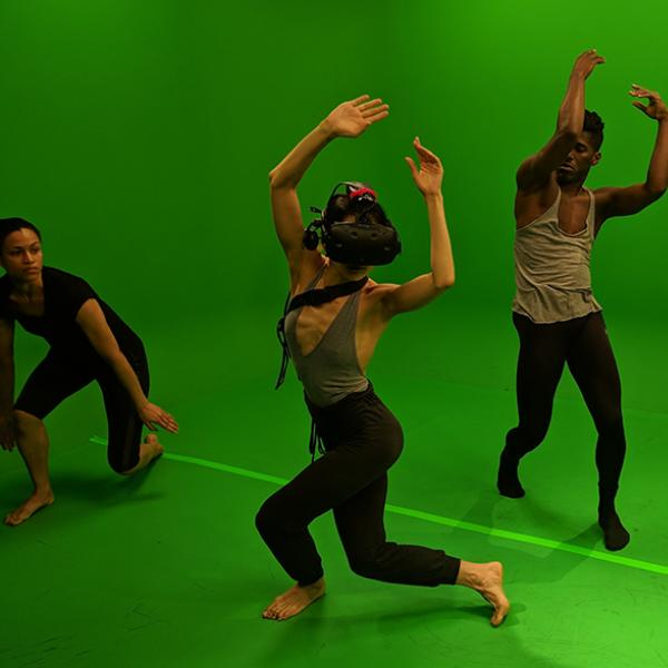 A dancer wearing virtual reality headgear performs with other dancers in a green room