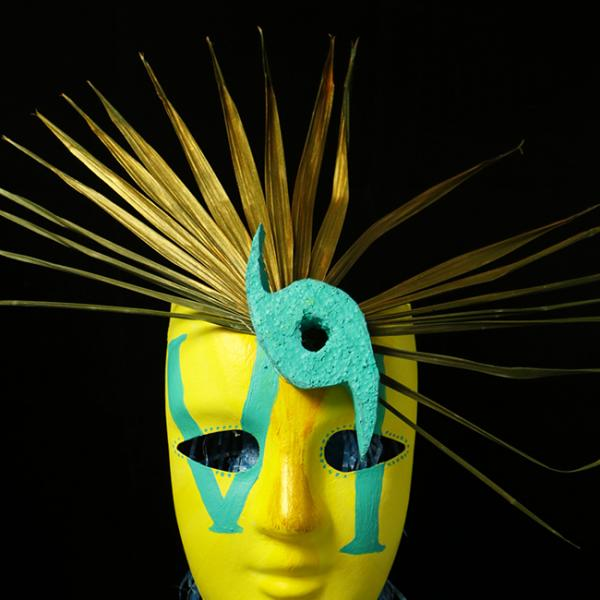 "A yellow mask with ""VI"" painted on it in teal with gold palm fronds branching off the top and a teal hurricane eye on one side"