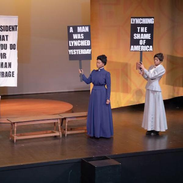 Three actresses portray suffragettes in a scene from a play