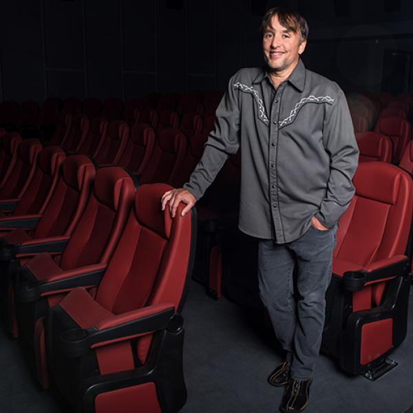 Man standing while holding onto red theater seats