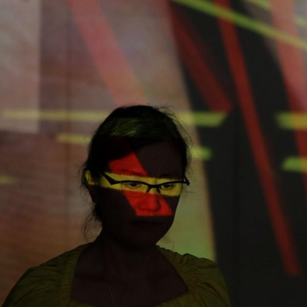 Woman in glasses with colored lights reflected on her.