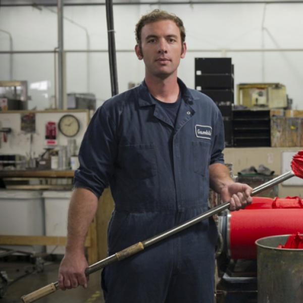Man standing in front of paint rolling machinery holding a pole with red paint on end.