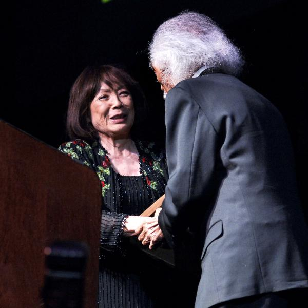 Japanese woman shaking hands with white-haired man in suit on stage.