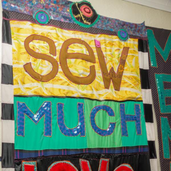 A colorful quilt that says Sew Much Love