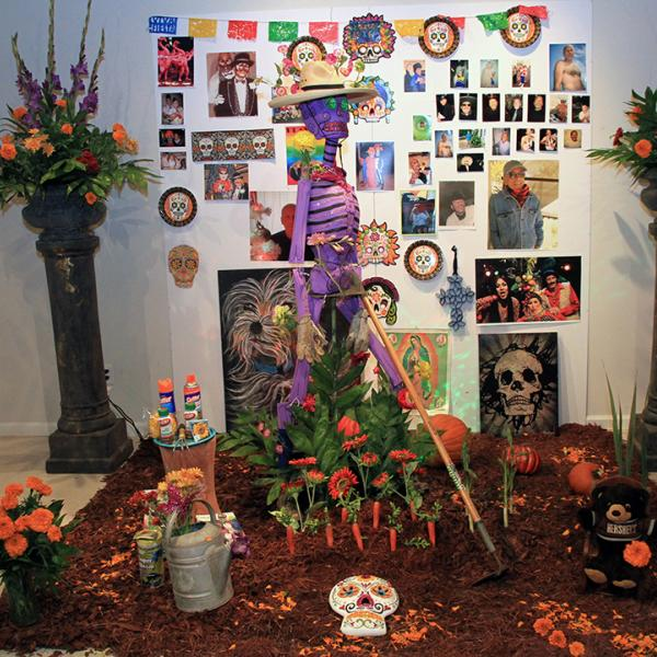 An altar for a Day of the Dead celebration with a purple skeleton, orange flowers, and a poster with photos on it.