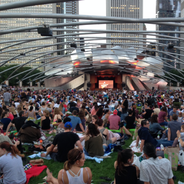 The silver Pritzker Pavilion in with audience in front sitting on grass