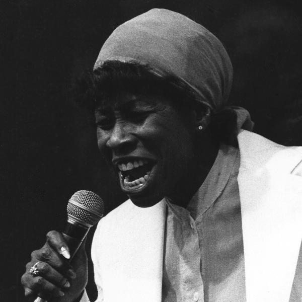Woman with kerchief on her head singing into microphone.