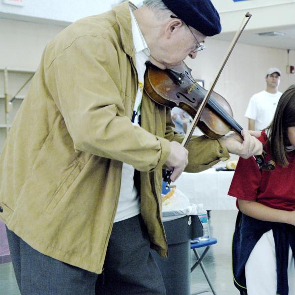 An elderly man playing violin to a couple of children.