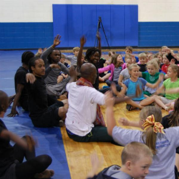 Dancers sit on floor leading a group of young children in movements