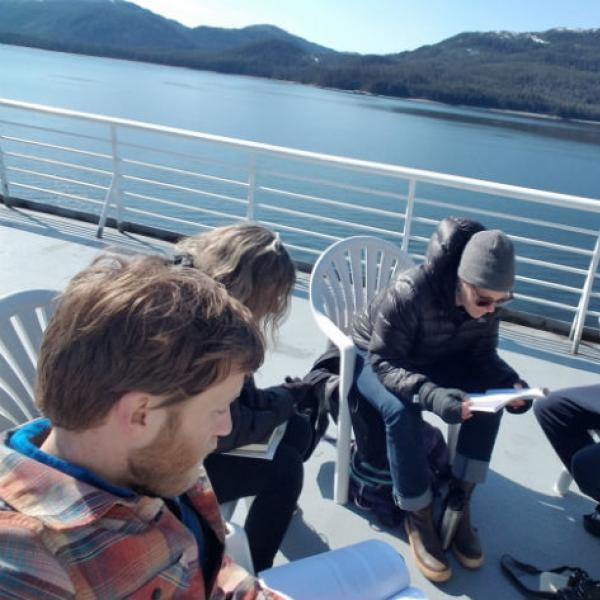 People reading papers sitting on the deck of a ferry in Alaska