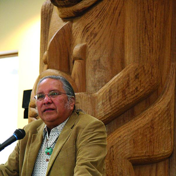 Native-American man at podium in front of large wooden carving.
