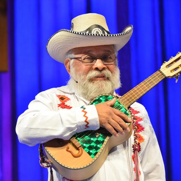 Musician with white beard in white suit and hat holding small guitar.