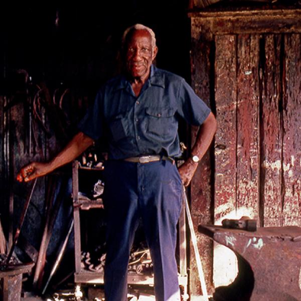 Man standing next to a fire for blacksmithing.