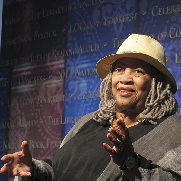 Toni Morrison wearing hat, sitting and gesturing with her hands