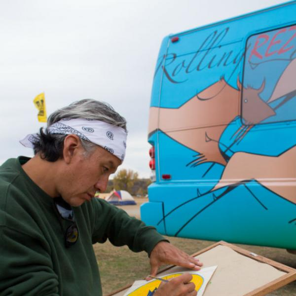 A man in bandana does a watercolor painting in front of a colorful bus