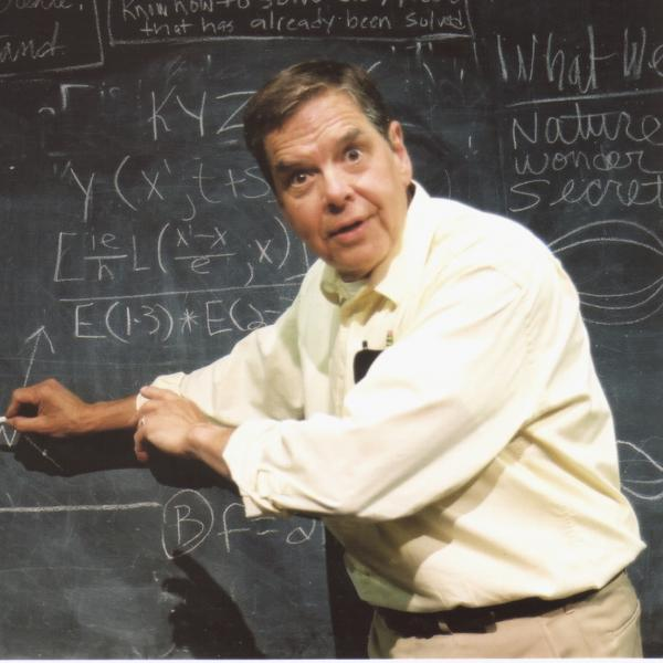 Man standing at chalkboard full of mathematical equations.