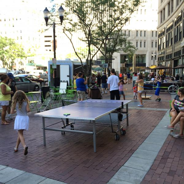 People on the sidewalk of a city doing hula hoop near a ping-pong table.