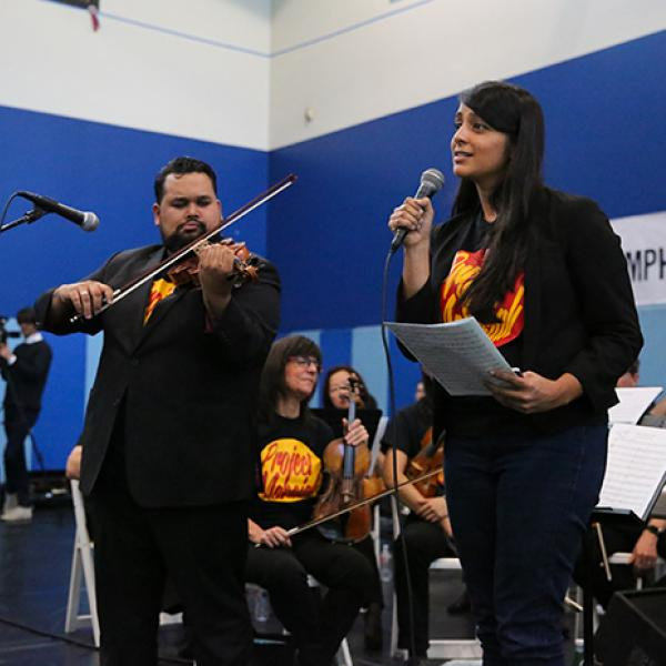 A man playing a violin stands next to a woman speaking into a microphone