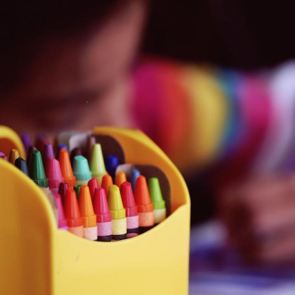 a photograph which highlights a box of crayons next to a child in the background