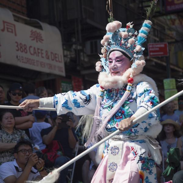 a performer during a parade wears traditional Chinese dress