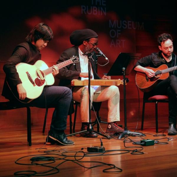 a group of three musicians performing on stage