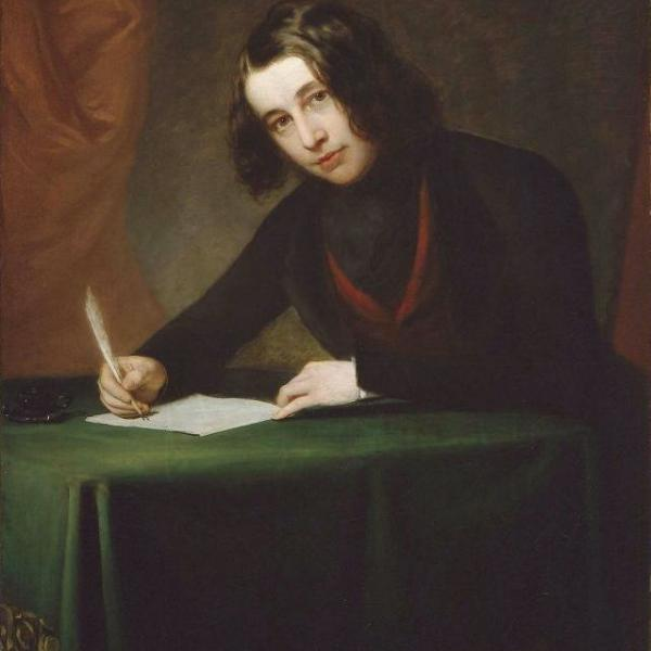 19th century portrait of a young Charles Dickens who sits over a desk covered with a green cloth writing
