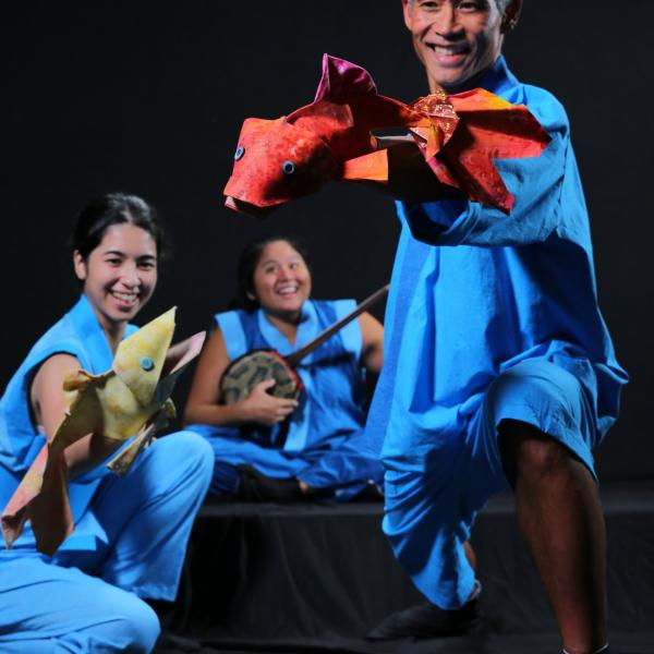Actors dressed in flowing blue outfits hold fish puppets and a banjo while performing a traditional Japanese fable