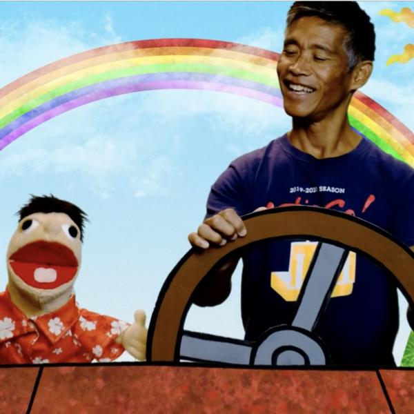 A smiling man sits next to a puppet while they drive in an animated car