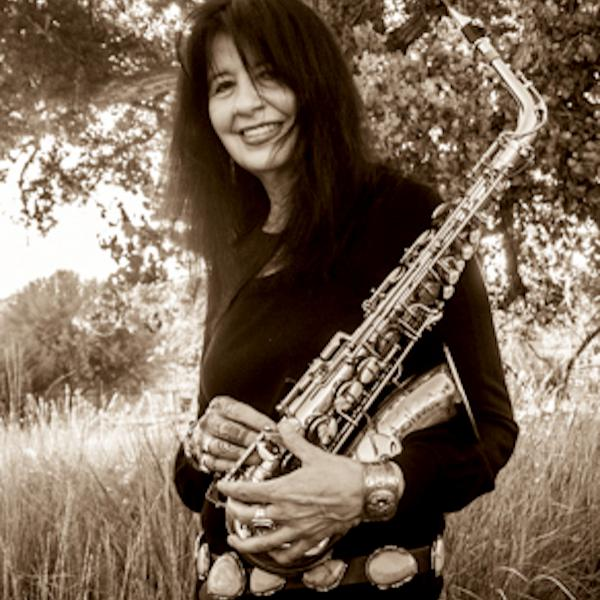 A woman in a field holding a saxophone.