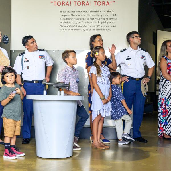Men in military uniforms, women, and children dressed in red, white, and blue standing in a museum
