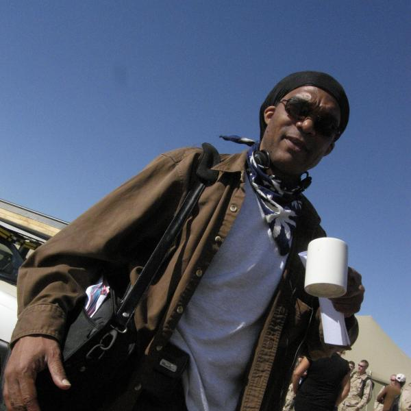 Man wearing sunglasses outside holding coffee cup.
