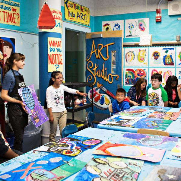 Students stand around a table with art work while a teacher holds up another piece of art work for them to see