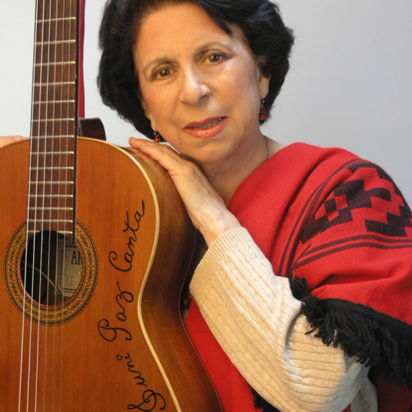 A woman poses with a guitar.