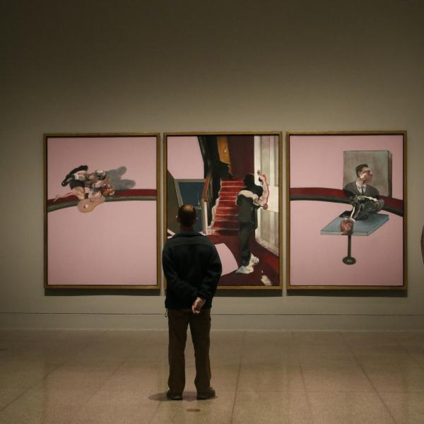 Masked museum visitors look at three large paintings by Francis Bacon
