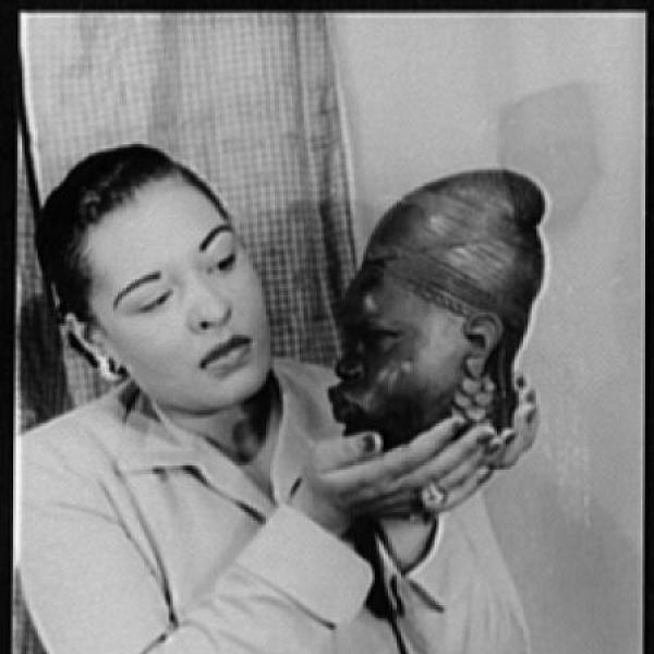 black and white photo of Billie Holiday who is shown from the waist up and stands holding an African mask
