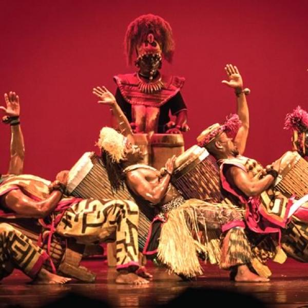 African drummers onstage in traditional costume leaning back in a dance pose with a tall man behind against a red background