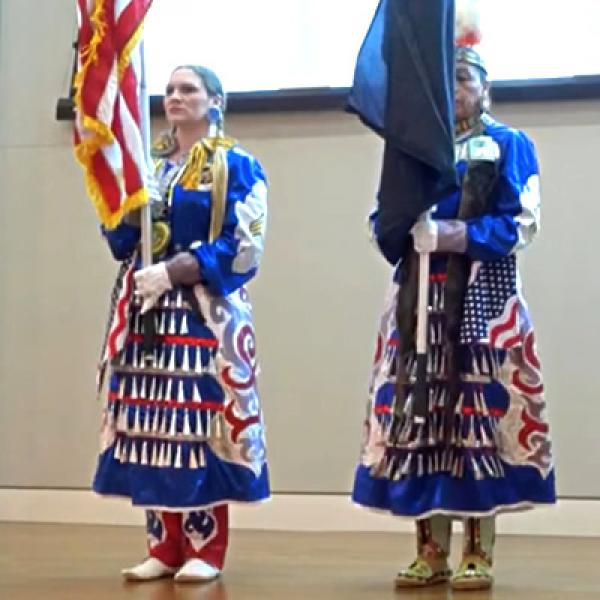 Two women in native american traditional dress on a stage, one holding a U.S. flag and the other holding a tribal flag