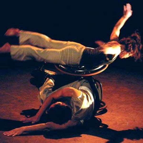 An able bodied dancer laying across a wheechair dancer