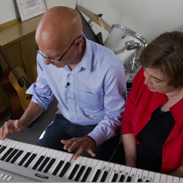 A music therapist  works with a patient recovering from a stroke