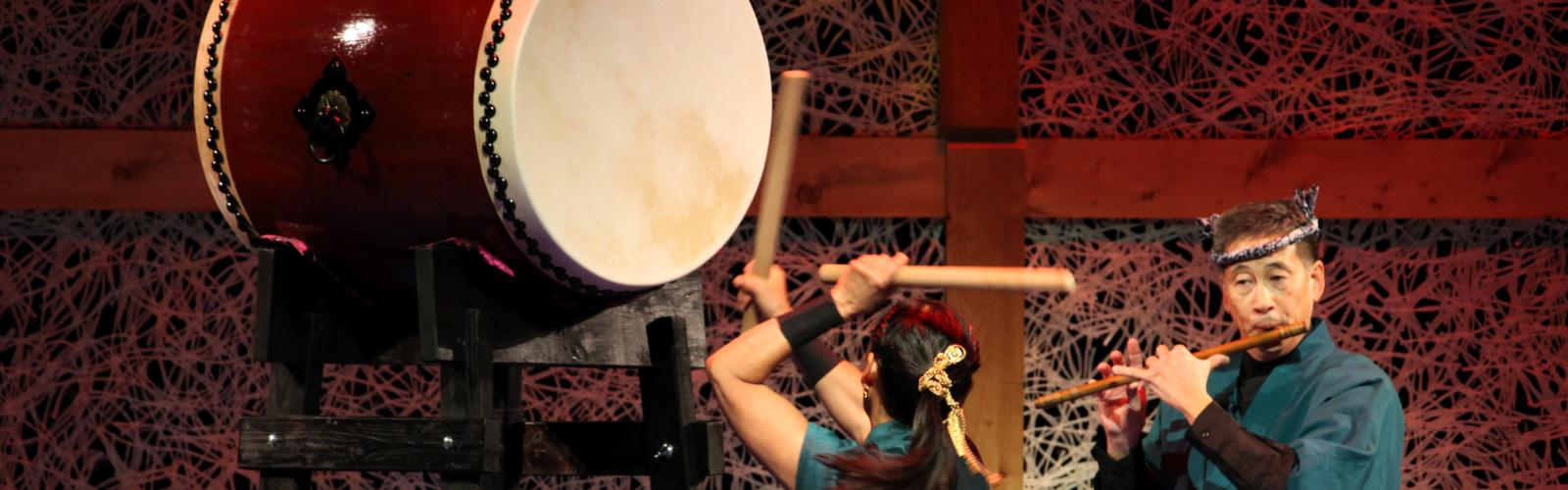 Woman banging a large drum while man plays flute on stage.