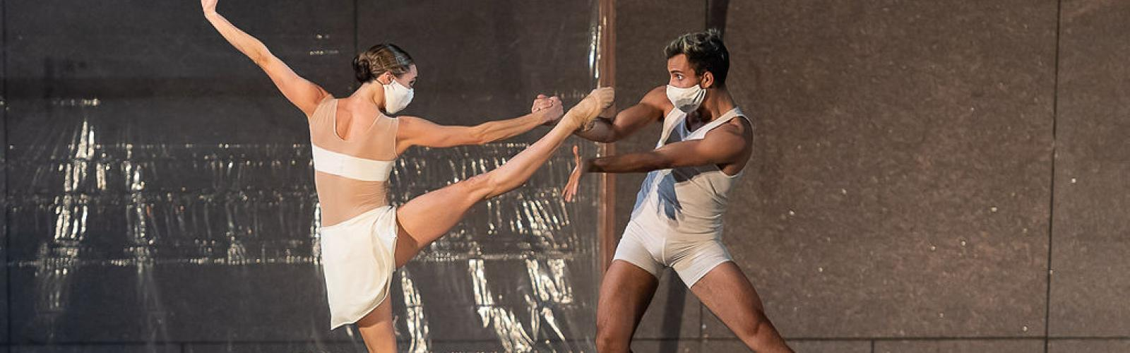 Woman and man dancing on stage wearing masks.