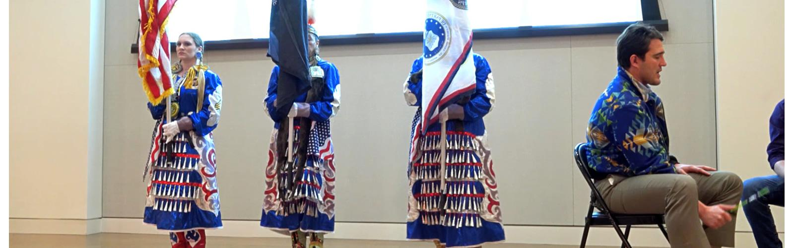 Three women in native american traditional dress holding the US and two native american flags on stage