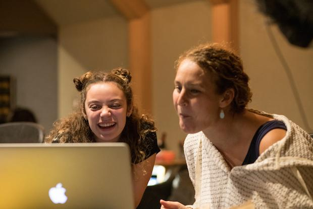 Two women laugh, looking at a laptop screen in a recording studio.