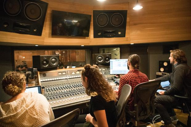 Two women and two men sit at a large mixing board in a recording studio, working.