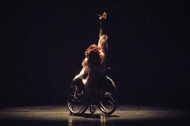 A dancer in a wheelchair lifts one hand upward as she performs onstage