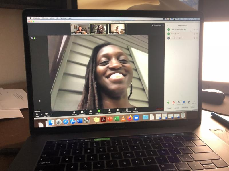 A laptop screen shows a video of a smiling woman with smaller pictures of the people she is speaking with above