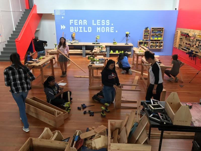 In a large open space, a group of high school girls construct furniture.