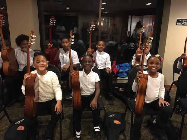 two rows of young students of color holding their classical guitars upright