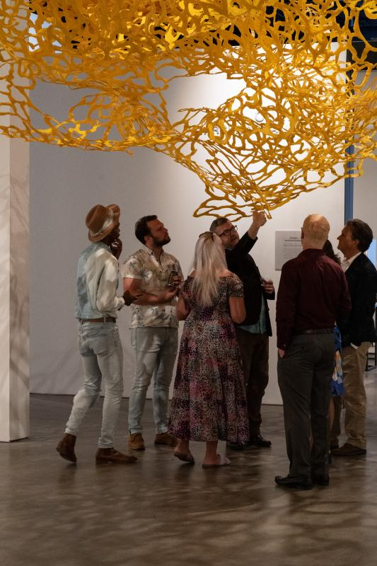 A group of people look up in a gallery at a lacy yellow sculpture installation