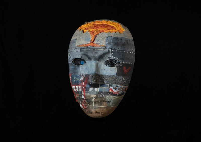 An intricately painted mask in mostly shades of grey with words of inspiration and hope